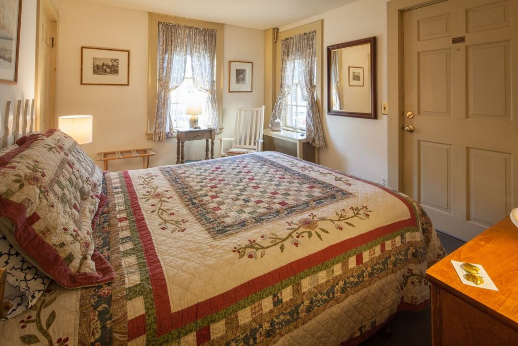 The Deck Room, overlooking part of the garden, is located on the first floor. It features a queen size bed and shares a bath with the Path Room. Marblehead art and artifacts decorate the Deck Room as well as walls throughout the B&B.